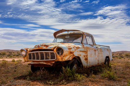 An old rusting relic of a ute left in scrub of Australian outback desert. Banque d'images