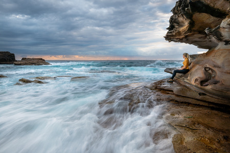 Watching the waves rush by from a little cave overhang on the Sydney coast