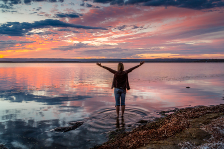 Female with arms outstretched enjoys the sunset turning the sky shades of red and mirrored reflecting colours in the water.