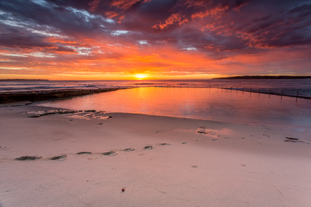 Glorious sunrise with ocean rock pool and beach.  Surfers waiting to catch a wave.  Cronulla Australia