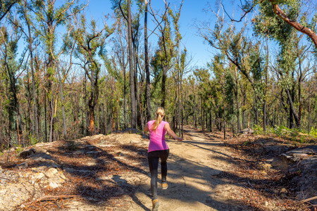 Woman running along a dirt trail in forest wilderness area