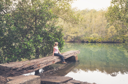 Sitting on a rustic large hewn timber jetty very worn and weathered in remote bushland creek Australia Banque d'images