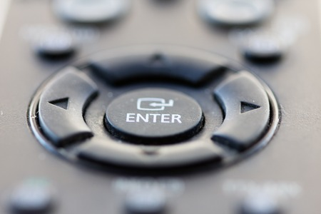 desired: The ENTER button of a remote control is to get into the desired function for the settings of TVs and DVD players. Stock Photo