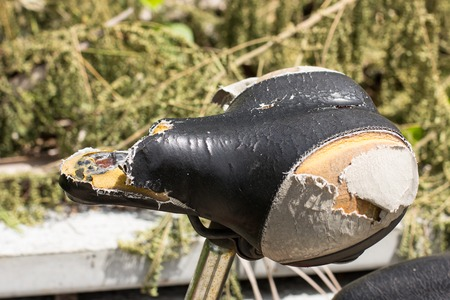 outworn: A bike has been used for years and parked outdoor. Its saddle is outworn to the sponge inside.
