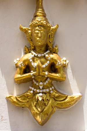token: Golden Deva deity clasping hand in token of worship. The sculpture is respectfully engaged on walls at places of importance, such as temples.