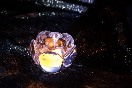 crystal glass: A candle is lit in a crystal glass holder. Yellowish light of the candle delivers a warm tone atmosphere.