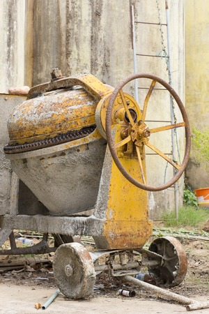 driven: Concrete mixer with a wheel for pouring ready-mixed concrete onto a tray. This mixer is driven by an electrical motor.