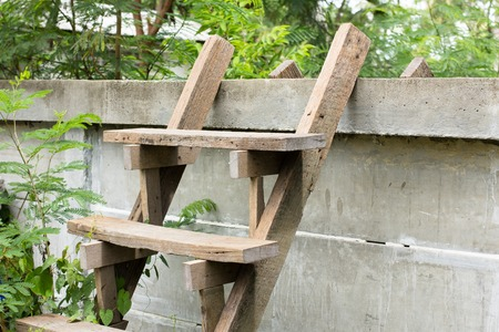 crack climb: Wooden ladders are placed for climbing over concrete fence between the houses next to each other for short access.