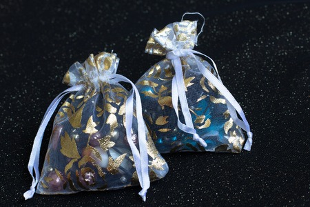 earing: Cute fabric bags decorated with gold motifs containing a gift such as ring, earing and necklace. Stock Photo