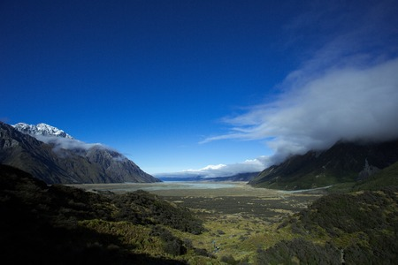 upstream: Upstream of famous Lake Pukaki of New Zealand, looking from the Tasman lake. Big cloud is rounding the mount Sealy and soaring the South.