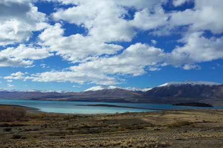 dominant: Lake Tekapo of New Zealand in beautiful turquoise blue, is more like a painting than real. It is dominant among brown dry grass, and dark-toned color of mountain ridges.