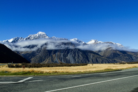aoraki mount cook national park: Long big clouds rounding mountain peaks at the entrance to the Tasman Lake. This area is a part of the Aoraki Mount Cook National Park in the South Island of New Zealand.