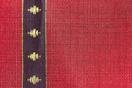 enriched: A beautiful piece of very fine Thai silk of blue stripe on red background design. The blue stripe is enriched with yellow diamond-shaped objects at the center.