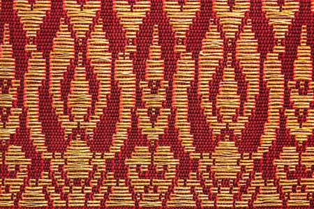 prong: A beautiful piece of very fine Thai silk of golden prong on red and black background.