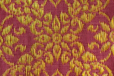 thai silk: A beautiful piece of very fine Thai silk of golden flower-liked design on pink and brown background.