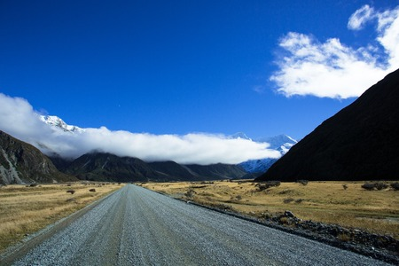 aoraki mount cook national park: Access to the Tasman Valley of Aoraki Mount Cook National Park, is a gravel road. A long big cloud rounding the mountains, is usually seen in the area. Stock Photo