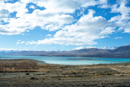 ridges: Lake Tekapo in beautiful turquoise blue, that is caused by glacial flour, fine rock particles from the glaciers. The lake is dominant among brown dry grass, and dark-toned color of mountain ridges.