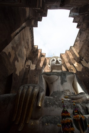 pointed arm: Lord Buddha image was respectfully engaged placed at an ancient temple called Wat Srichum, that was built about 700 years ago in Sukhothai. Temples open roof lets morning light shine through, and brighten Lord Buddhas face. Stock Photo