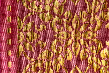 A beautiful piece of very fine Thai silk of golden flower-liked design on pink and brown background.