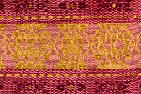 enriched: A beautiful piece of very fine Thai silk of yellow spheres on pink background at the center. Two red stripes on the edges, are enriched with yellow dash lines.