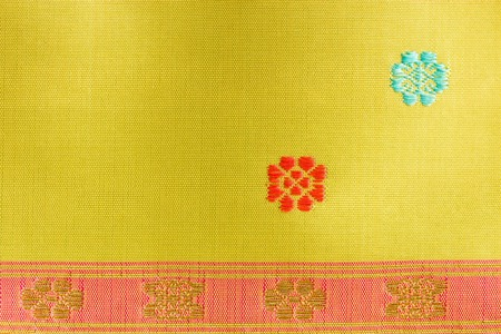 A beautiful piece of very fine Thai silk of golden stripes on pink band, and orange and blue flowers on light green background.