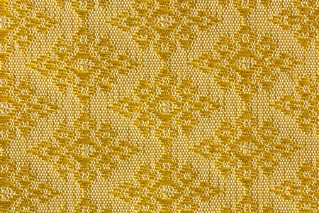 A beautiful piece of very fine Thai silk of golden diamond-shaped on yellow and white background. Standard-Bild