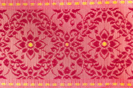 A beautiful piece of very fine Thai silk of red flowers on pink background. The design is enriched with yellow dash lines.