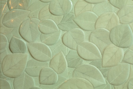 The bathroom wall is decorated with tiles, that are painted light grey leaves.
