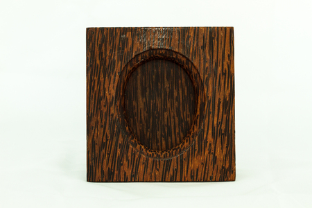 The picture frame made of wood, is upright shaped. The display at the center, is oval shaped.
