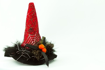 The pointy hat is composed of red and black sections. The red, is decorated with cobweb and strands. The black, is decorated with feather and ribbons. The hat is used for the Halloween, or fancy parties.