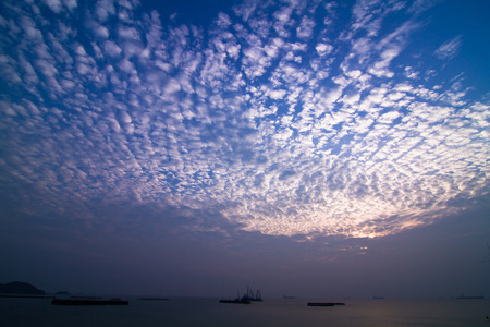 A group of light grey clouds during the sunset, are over commercial ocean liners at the shore of Sichang Island of Thailand.