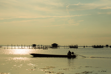 Folk of a fishing village in south of Thailand, is taking a long-tailed boat into the lagoon. Community of the lagoon of Songkhla, breeds sea bass in breeding nets that are supported by wooden poles.