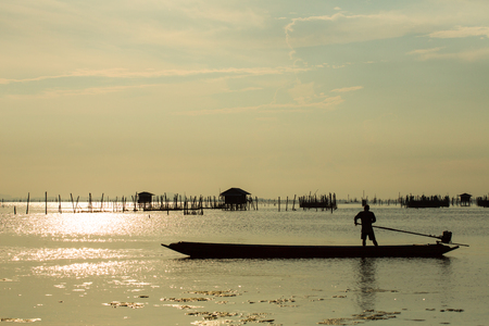 Folk of a fishing village in south of Thailand, is positioning the boat's propeller. Community of the lagoon of Songkhla, breeds sea bass in breeding nets that are supported by wooden poles.