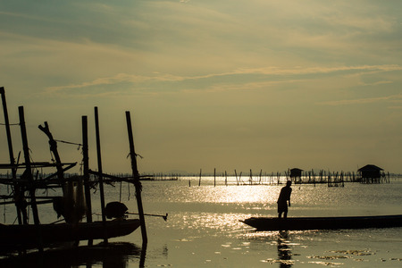 Folk of a fishing village in south of Thailand, is reversing his boat into the lagoon. Community of the lagoon of Songkhla, breeds sea bass in breeding nets that are supported by wooden poles.