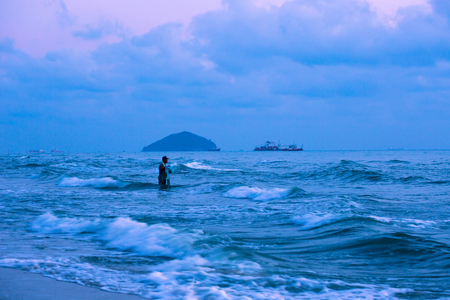 A fisherman is paying attention to the sea surface. He is holding a fishnet, ready to cast the net as soon as mass of near-shore fish emerging the surface. This activity is an early morning fishery. Standard-Bild