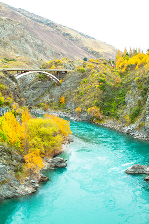 Kawarau river drains Lake Wakatipu, is closed by Queenstown in New Zealand. The Kawarau Gorge Suspension Bridge crossing the river, is the site of the world's first commercial bungy jumping operation. Standard-Bild