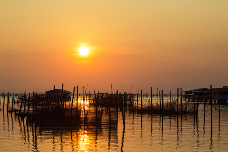 The lagoon of Songkhla, is located in the south of Thailand. Community around the lagoon are fishing villages, that breed sea bass in breeding nets supported by wooden poles. Standard-Bild