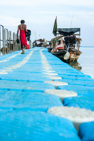 A folk in the Andaman Sea of south of Thailand, is walking to his long-tailed boat used as the camp and fishery. In the high season, the boat provides tour services including snorkelling. Standard-Bild