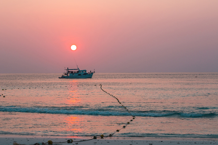 A diving boat is docking at the front beach, and ashore its passenger to the Similan Island watching the sunset. The Similan Island is one of a group of nine islands in Andaman Sea of South Thailand.