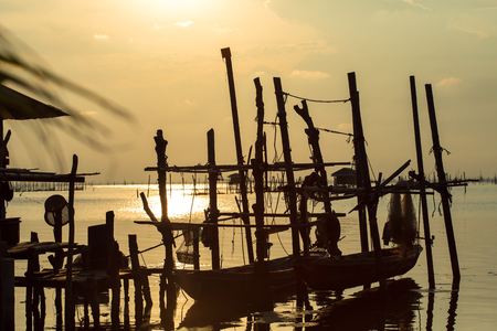 long tailed boat: A long-tailed boat is laid on the boat rack while off-duty. The owner shall take his boat off the rack into the lagoon, to feed his fish or fix the equipment. This fishing village is located in Songkhla of south Thailand, where the community breeds sea ba Stock Photo