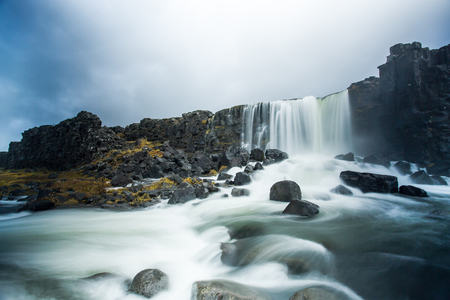 Oxararfoss is located in Thingvellir National Park, not far from Reykjavik. Stream of water flows down a steep cliff. On a rainy day, the waterfall is distinct from the cliff and surrounding rocks.