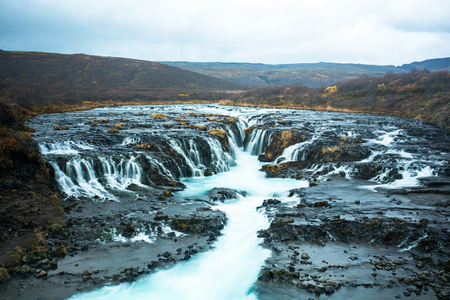 Bruarfoss or waterfall bridge, consists of numerous runlets falling into a chasm at the middle. At the chasm, the water of Bruara river is colored in glacial blue running on black volcanic bedrock.
