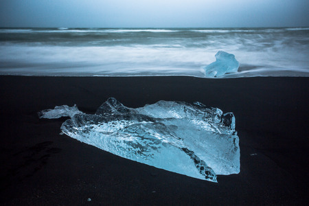 Blocks of ice in bright blue, drift out to sea and are washed up on black sand beach of Iceland. These ice blocks once were parts of icebergs that released from the nearby Jokulsarlon lagoon. Standard-Bild