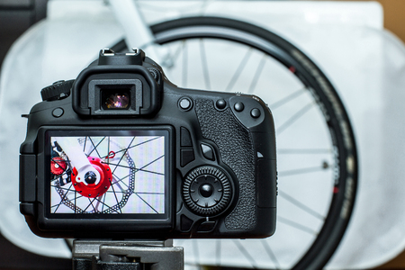 Live preview of a bike hub photoshooting, is displayed on a DSLR's LCD monitor. The bike hub in bright red is installed with disc brake, that removed off the forks with a quick release lever skewer.
