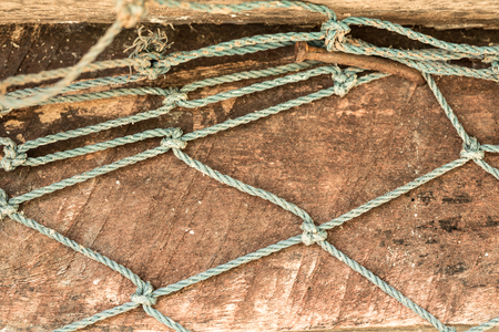 sheet metal: Rope mesh is pinned to the wood of a simply-made coop with a nail, to prevent chickens from escaping. Villagers in the countryside of Thailand breed chickens to collect eggs, usually in the morning.