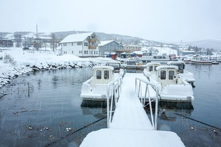 Fishing boats are moored at Hansnes pier during the winter, and covered by snow. Hansnes is a village located along the Langsundet strait, about 58 kilometers northeast of the city of Tromsø. Standard-Bild