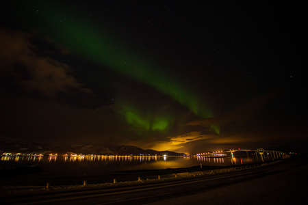 Green northern lights are soaring over a bridge near Stokmarknes in northern Norway. The green color is caused by electrons from space collide with oxygen molecules in the atmosphere. Standard-Bild