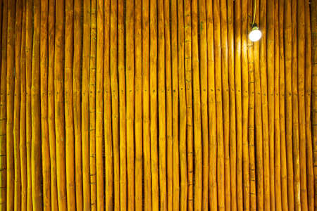 A hut has a wall made up of bamboo trunks that are straight and the same size. These trunks were cut to equal length and applied with a coating, then fix them to the transverse wood with nails. Standard-Bild