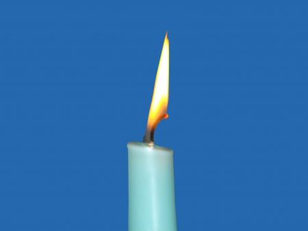 light blue candle against blue background Stock Photo