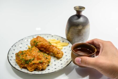 A mans hand is raising a sake cup to drink, a white table with fried chicken and potatoes in a polka dot dish. Is a Japanese style meal.